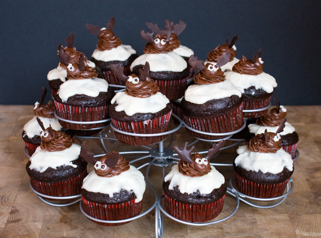 Picture of cupcakes on a stand decorated with moose made from chocolate frosting and chocolate.