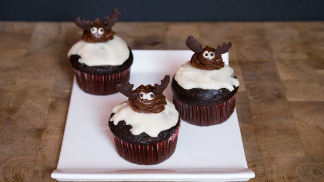 Picture of cupcakes on a square plate decorated with moose made from chocolate frosting and chocolate.