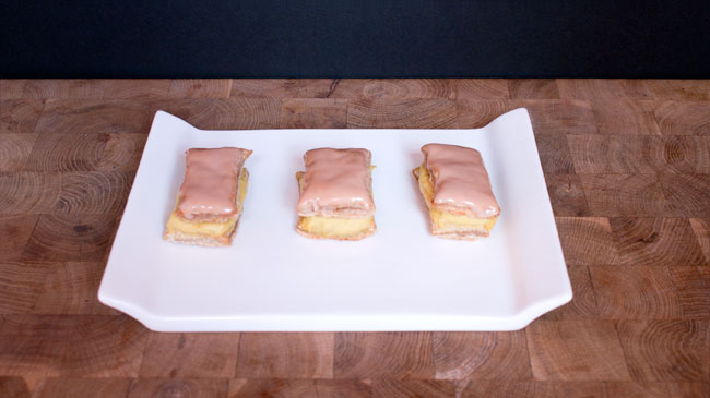 Picture of three mini-tompoezen on a plate with pink frosting.