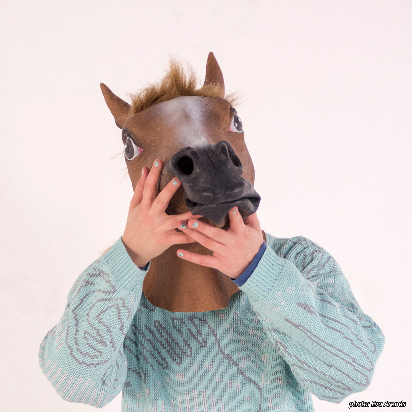 Picture of a character (Horseboy) from the waist up in a light blue retro polyester sweater with abstract design. His nails are painted a similar color and he wears a latex chestnut horse mask. He has his hands closed under his jaw as though he has just said something regrettable.