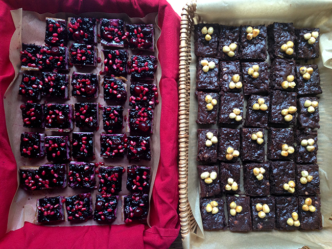 Picture of two baskets with baked goods, one with berry cheesecake topped with pomegranate seeds, one with brownies topped with three caramelised hazelnuts each.