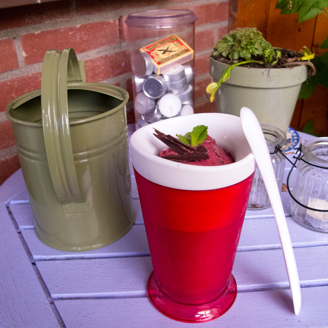 Picture featuring a round container (the zoku shake maker) filled with bright pink raspberry sorbet garnished with two mint leaves and a few chocolate shavings.