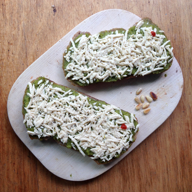 Picture of two open-faced sandwiches with mint-pea spread and melted daiya.