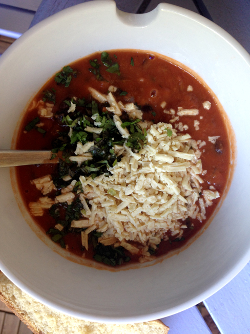 Picture of a bowl of chili topped with shredded daiya.