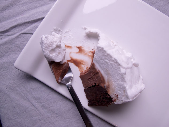 Picture featuring a cut out piece from a semi-spherical baked alaska with a brownie base, chocolate ice cream center and thick meringue outer layer.