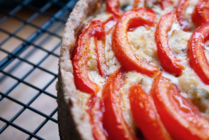 Close-up picture of a quiche with tomato slices arranges in a circular pattern. The quiche sits atop a cooing rack with small black metal squares that contrast with the table underneath it.