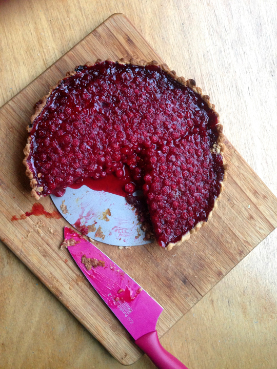 Picture of a redcurrant pie on a wooden cutting board on top of a wooden background. One-fifth has been cut out with a magenta knife also pictured.
