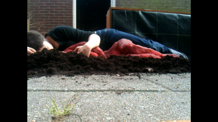 Untitled performance still featuring a red puppet lying on its side on a layer of earth. Behind the puppet a figure dressed in jeans and a black shirt is spooning the puppet.