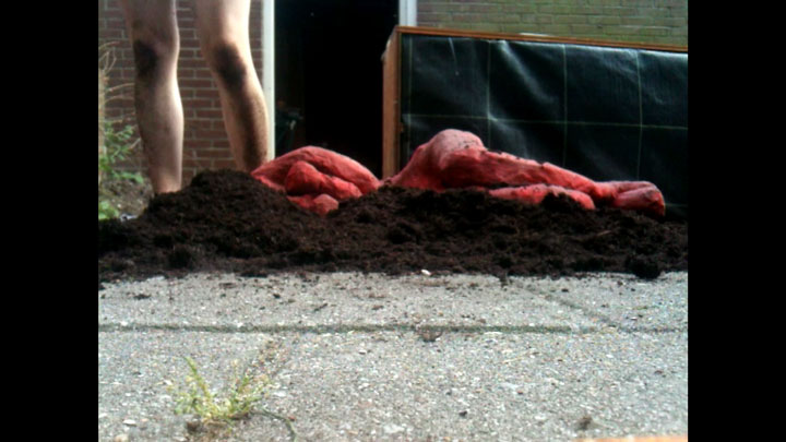 Untitled performance still featuring a red puppet lying on its side on a layer of earth. Behind the puppet stands a naked figure pictured up to the mid thighs. Their knees and shins are covered in black earth, contrasting with the grey stone surroundings and pale legs.