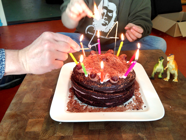 Picture of a layered schwarzwalder kirsch birthday cake featuring a lot of candles and a 24 in sparklers.