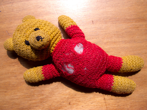 Picture of a yellow and red cotton knit teddy bear with two holes in his rump.
