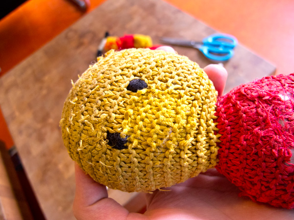Close up picture of the head of a red and yellow cotton knit teddybear without ears and nose.