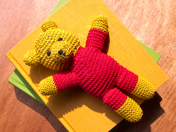 Picture of a yellow and red cotton knit teddy bear on a pile of cookbooks.