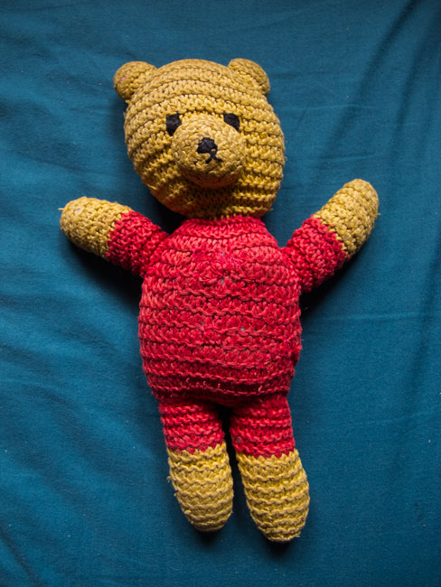 Picture of a yellow and red cotton knit teddy bear on a turquoise background.