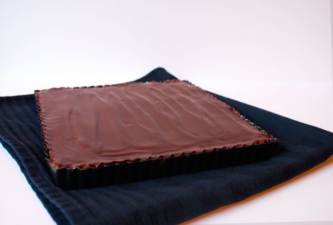 Picture of a square baking tin filled with millionaire's shortbread on a white and black background.