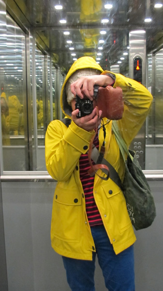 Mirror selfie of a person in a bright yellow raincoat, blue pants and red striped sweater.