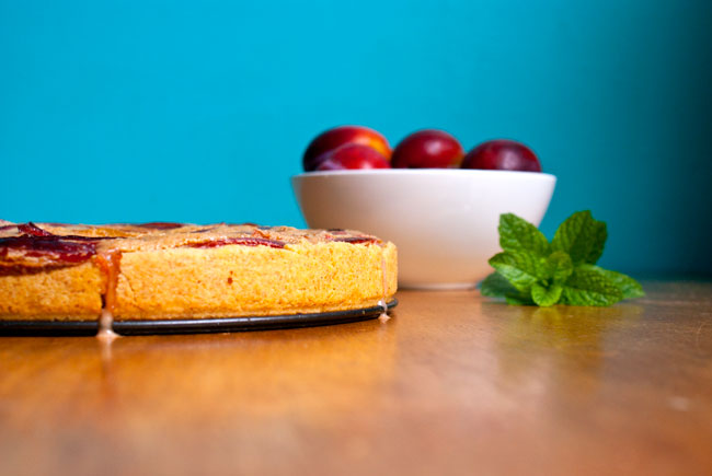 Picture of plum tart on top of a wooden table in front of a blue background with some whole plums and mint leaves in the background.