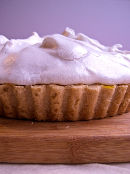 Close-up of the outside of a lemon meringue pie in front of a grey background.