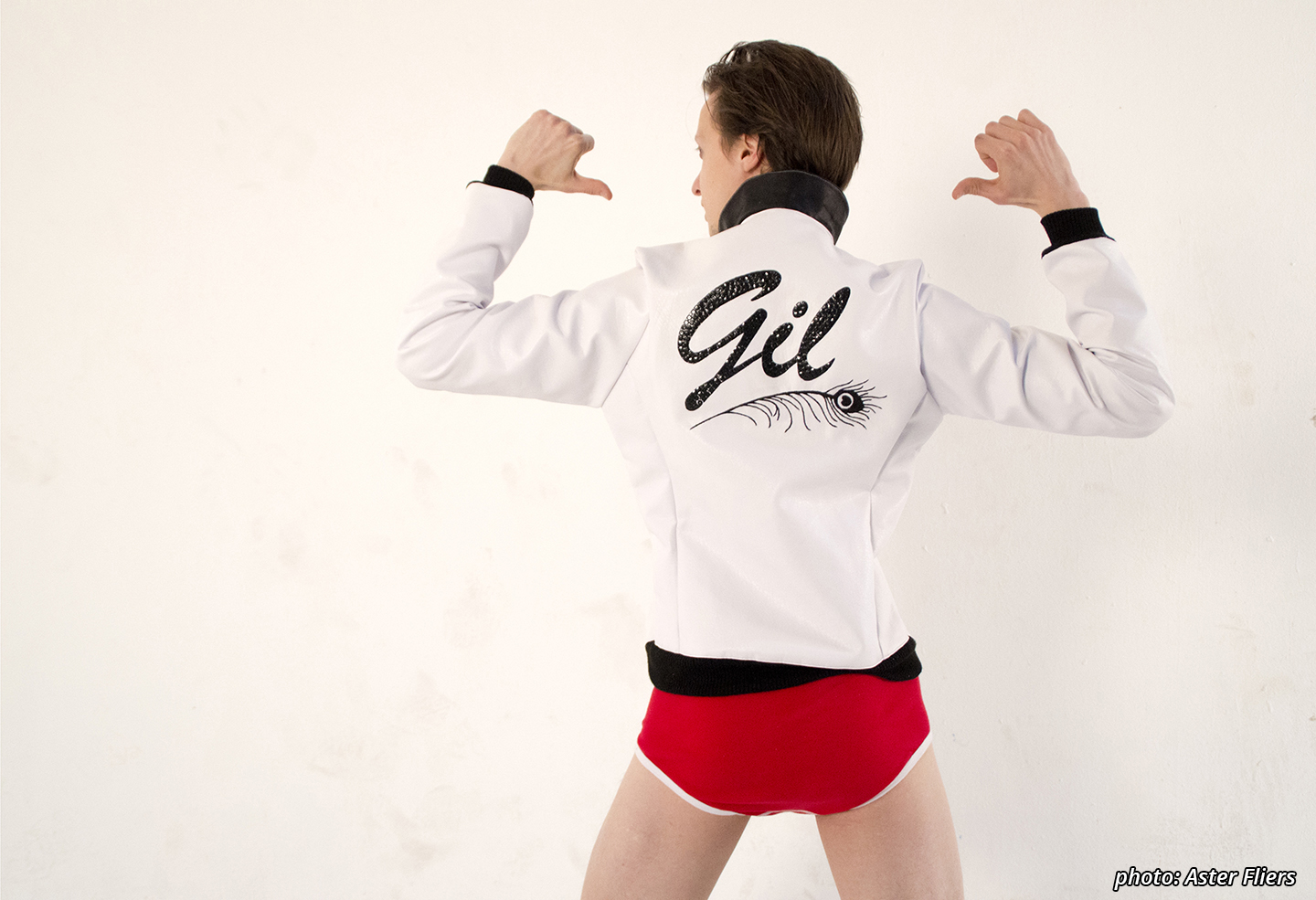 "Picture featuring a character (Gilminder) shown from the mid-thigh up dressed in red underpants and a white leather jacket with black cuffs and collar, a red and black pocket lining and the word ""Gil"" emroidered in black glitter on the back above a hand-stichted equally black peacock feather. the character is facing away from the camera, showing of the embroidered pattern and pointing to it with both thumbs."