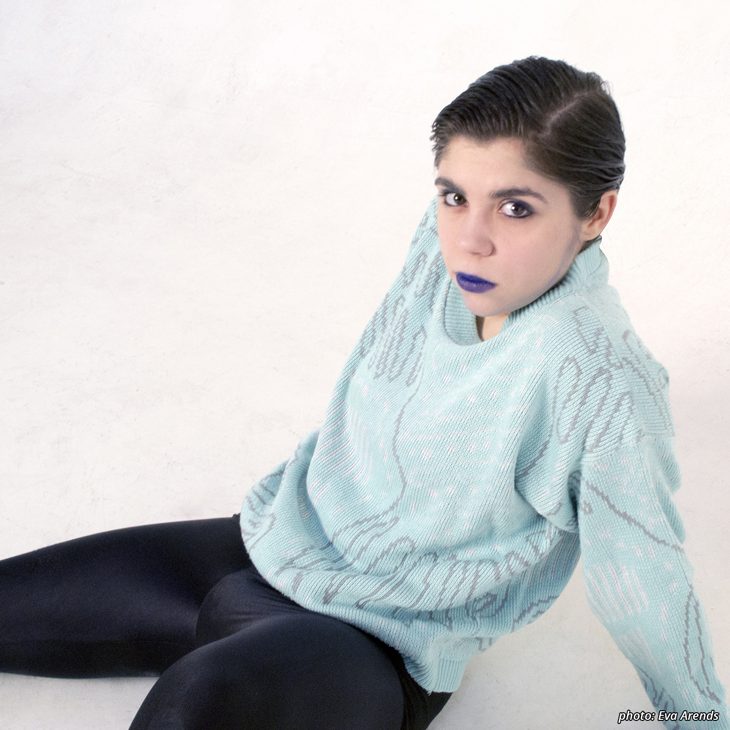 Picture of a character (Horseboy) photographed in profile, turning his head to look stright at the camera. The character has gelled hair that's combed back, blue lipstick, black and blue eyeliner and is wearing black leggings and a light blue jumper with abstract grey pront and white dots.