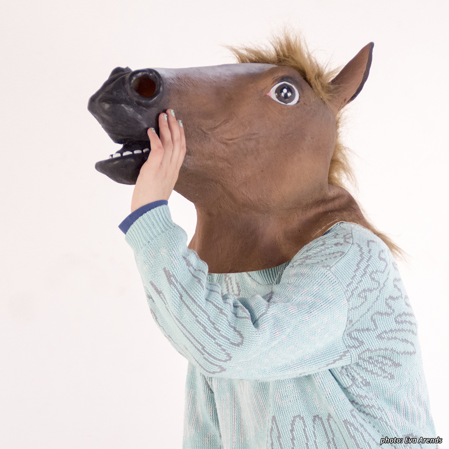 Picture of a character (Horseboy) from the waist up in a light blue retro polyester sweater with abstract design. His nails are painted a similar color and he wears a latex chestnut horse mask that is visible in profile. He has his hands next to his open mouth as though he is amplifying something he is shouting.