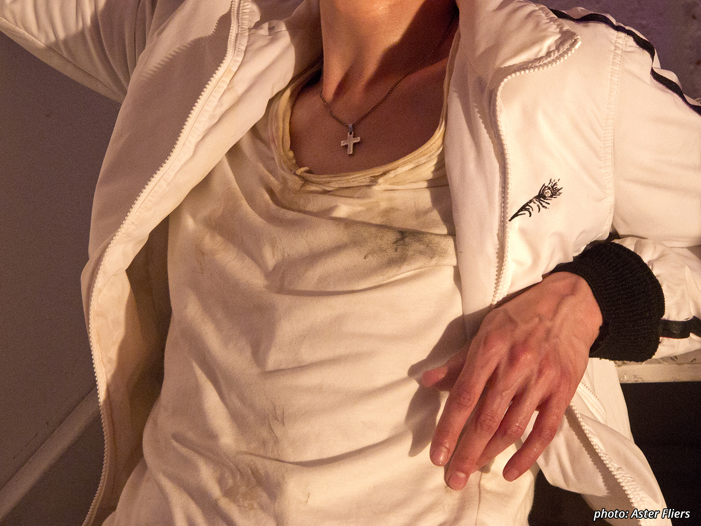 Close-up of a character's upper body, without the head. He's wearing a white, stained t-shirt and white jacket with black details. There's a small silver cross on a silver chain around the neck.