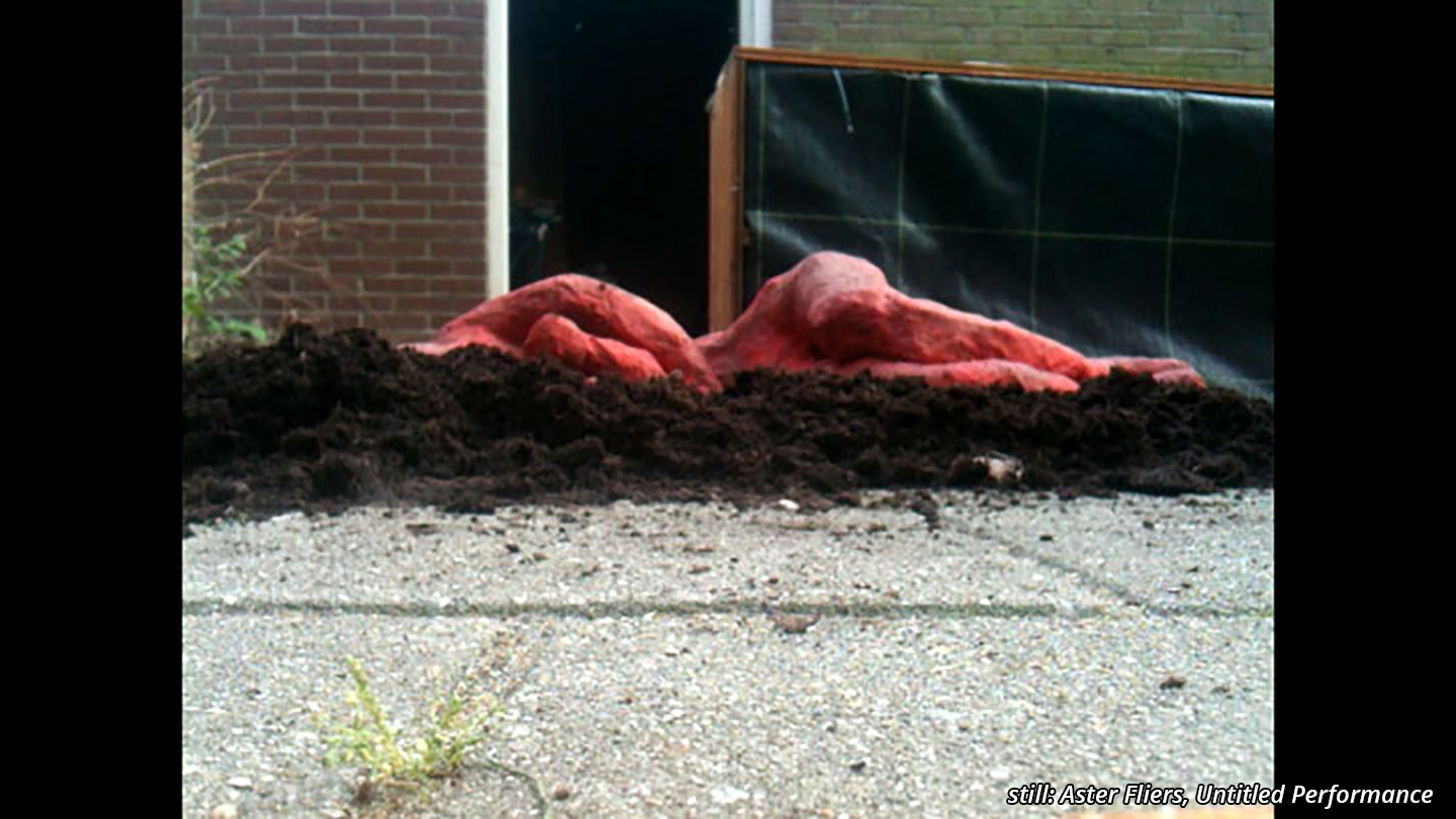Untitled performance still featuring a red puppet lying on its side on a layer of earth.