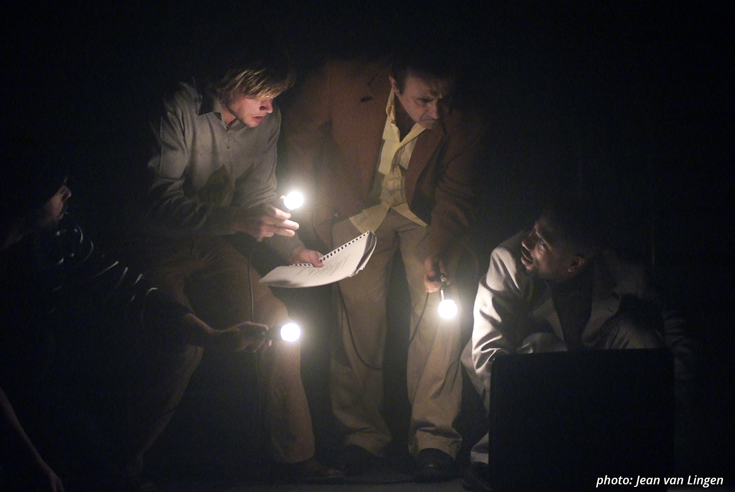 Four characters, all dressed in some form of suit or pants-sweater-combo, beding over an opened suitcase in the right lower corner. Three of them are holding a lightbulb that's attached to a black cord, using it to shine light into the suitcase for the forth character sitting behind and bent over the suitcase.