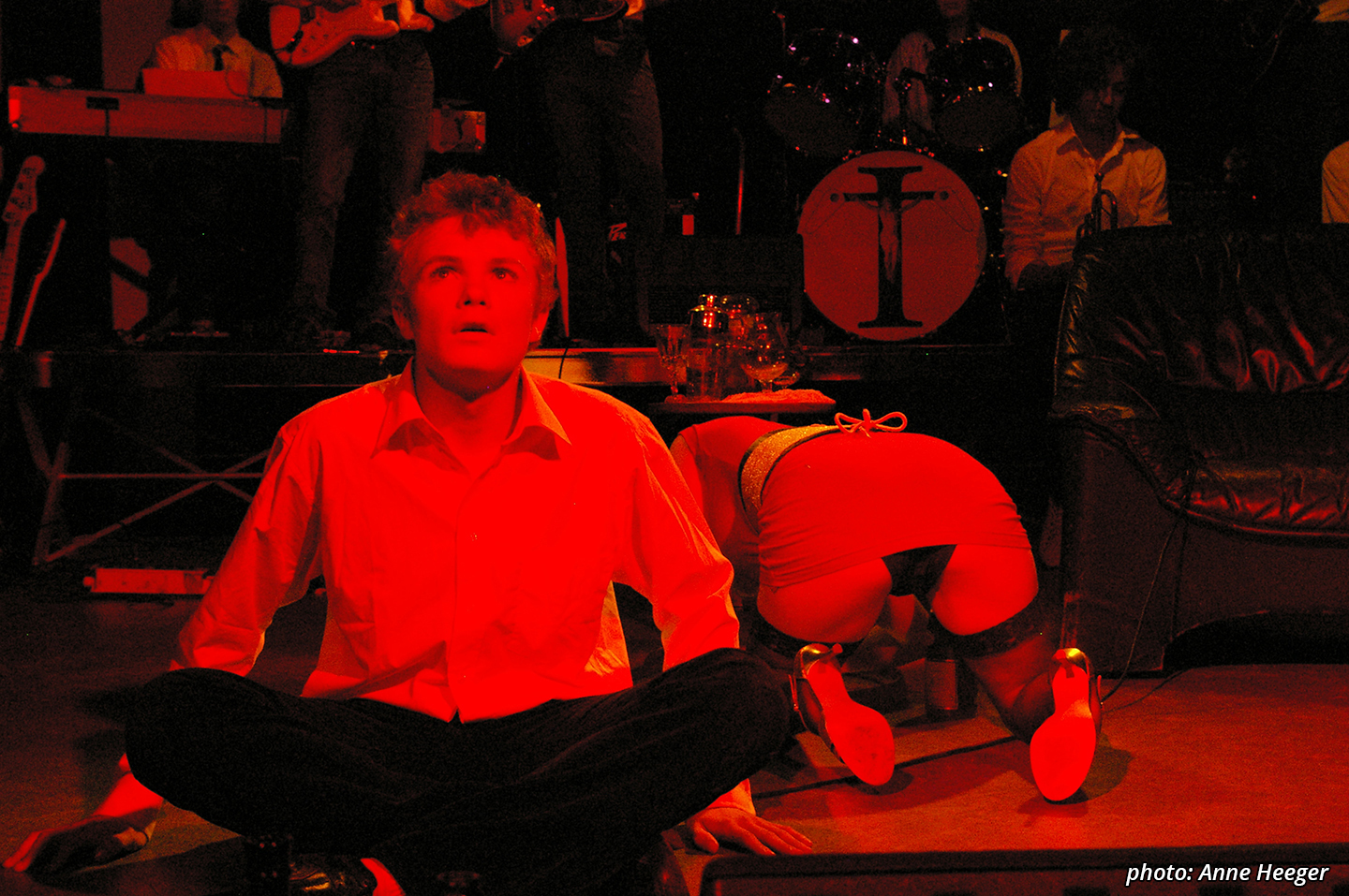 Picture featuring a character (Tommy) dressed in a white shirt and dark pants, sitting cross-legged staring up and away from the camera. Both his hands are on the floor. Right behind him we see a character (Acid Queen) dressed in stockings, a red and gold dress and gold patent stilettos. She's turned with her back to the camera, positioned on all fours, exposing her black underpants.